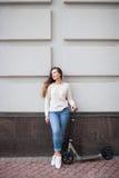 有站立在一辆单轮滑行车旁边的灰色墙壁的长的棕色头发的年轻美丽的女孩看起来去并且微笑 地方为 免版税库存图片