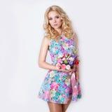 有站立在与淡紫色花花束的白色背景的卷曲金发的美丽的性感的谦虚甜嫩女孩  免版税库存图片