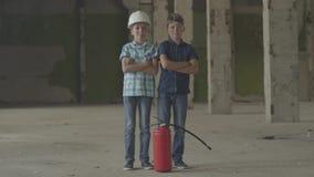 有站立在与看照相机的灭火器的被放弃的大厦的肮脏的面孔的两个小男孩 股票视频