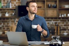 有站立在与膝上型计算机的桌上的咖啡杯的年轻人 免版税库存照片