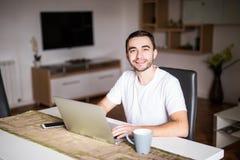 有站立在与膝上型计算机的桌上他的咖啡杯的沉思年轻人早晨 免版税库存图片