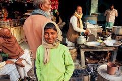 有站立在与茶masala供营商的室外咖啡馆的兴高采烈的面孔的男孩 库存照片