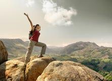 有站立在与被上升的ha的一座山顶部的背包的远足者 免版税库存图片