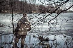有站立在丛林的猎枪的猎人人在用冰盖的河在春天狩猎期期间 库存照片