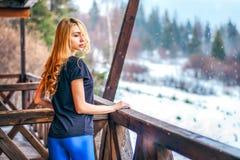 有站立在乡间别墅的一个木大阳台的长的卷发的俏丽的女孩 免版税库存照片