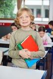 有站立在书桌的书的男小学生 库存图片