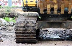 有站立在修理和扩展建造场所的铁锹的重的黄色履带牵引装置挖掘机路 免版税图库摄影