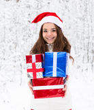 有站立在冬天森林里的圣诞老人帽子和红色礼物盒的青少年的女孩 库存照片