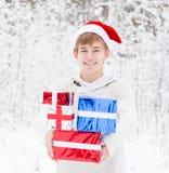 有站立在冬天森林里的圣诞老人帽子和红色礼物盒的青少年的男孩 免版税图库摄影