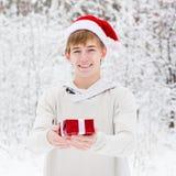 有站立在冬天森林里的圣诞老人帽子和红色礼物盒的青少年的男孩 库存图片