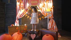 有站立在减速火箭的样式的老手提箱的卷发的小女孩 影视素材