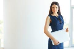 有站立在办公室的便携式计算机的女实业家 Busi 免版税库存照片