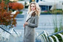 有站立在台阶的卷发的美丽的金发碧眼的女人户外在秋天 图库摄影