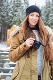有站立在台阶的照片照相机的美丽的妇女在冬天 免版税图库摄影