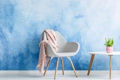有站立在咖啡ta旁边的淡色毯子的唯一扶手椅子 免版税库存照片