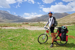 有站立在土耳其山的背景的一个大背包的骑自行车者 免版税库存照片