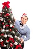 有站立在圣诞树后的圣诞老人帽子的人 免版税库存图片