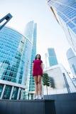 有站立在城市布局的凉快的样式的可爱的白种人妇女在现代办公楼附近 图库摄影