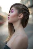 有站立在城市的桃红色构成的美丽的白肤金发的妇女 库存照片