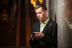 有站立在墙壁的一个手机的年轻人 库存照片