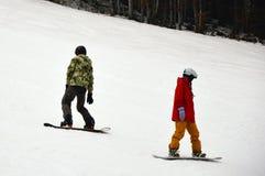 有站立在多雪的委员会的两块男性挡雪板下坡在Bukovel 库存图片