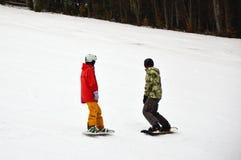 有站立在多雪的委员会的两块男性挡雪板下坡在Bukovel 免版税库存照片