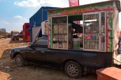 有站立在大柬埔寨啤酒党事件以后的微型商店的汽车 免版税库存图片