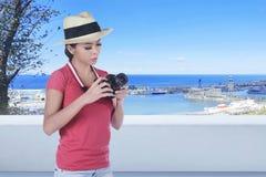 有站立在大阳台的照相机的年轻亚裔旅客妇女 免版税库存照片