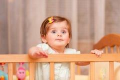 有站立在小儿床的簪子的小孩子 免版税库存图片