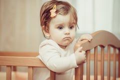 有站立在小儿床的簪子的小孩子 免版税库存照片