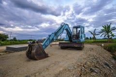 有站立在小山的铁锹的重的挖掘机 库存图片