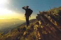 有站立在山上面的背包的游人在一个晴天享受谷的看法 图库摄影