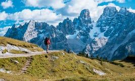 有站立在山的道路的背包的远足者 库存图片