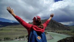 有站立在山边缘的背包和盖帽的年轻愉快的旅客女孩和在天空中投入他的手 backarrow 股票录像