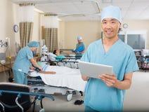 有站立在岗位手术的数字式片剂的护士 库存图片