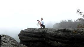 有站立在岩石观点和为有薄雾的早晨风景照相的三脚架的摄影师 国家公园撒克逊人Switzerlan 股票视频