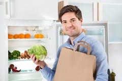 有站立在开放冰箱附近的食品杂货袋的人 库存照片