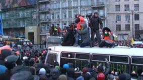 有站立在抗议的人群中的残破的公共汽车的照相机的新闻工作者 股票录像