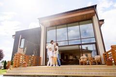 有站立在新房大阳台的孩子的家庭  免版税库存图片