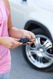 有站立在新的汽车附近的点火开关的无法认出的妇女 免版税图库摄影