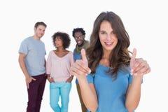 有站立在时髦的人民前面的拇指的妇女 图库摄影