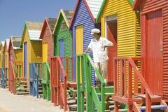 有站立在明亮的蜡笔色海滩小屋前面的白色帽子的人在圣詹姆斯,在印度洋的错误海湾,在海角T外面 免版税库存照片