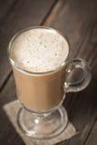 有站立在木桌上的温暖的拿铁的咖啡杯 库存图片