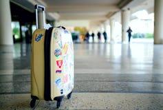 有站立在机场的许多五颜六色的贴纸的偶然手提箱 图库摄影