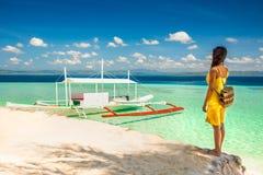 有站立在树荫ona海滩的黄色礼服的少妇  库存图片