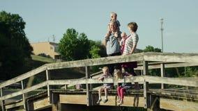 有站立在桥梁的四个孩子的愉快的家庭在公园充分的HD 股票录像