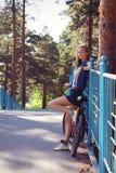 有站立在桥梁的自行车的少妇,放松 免版税库存照片