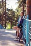 有站立在桥梁的自行车的少妇,放松 库存图片