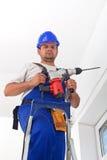 有站立在梯子的机械钻的工作者 免版税库存照片