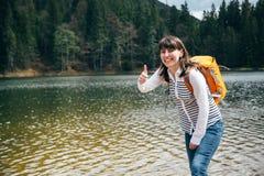 有站立在森林包围的山湖的银行的橙色背包的年轻愉快的微笑的女孩显示象与韩 免版税库存图片